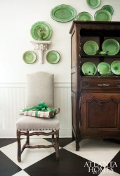 Color and pattern are at play in Ervin's Provincial-style kitchen and adjacent dining niche, with large-scale diamond-painted floors and a collection of green-glazed French pottery filling a 19th-century French vasselier.