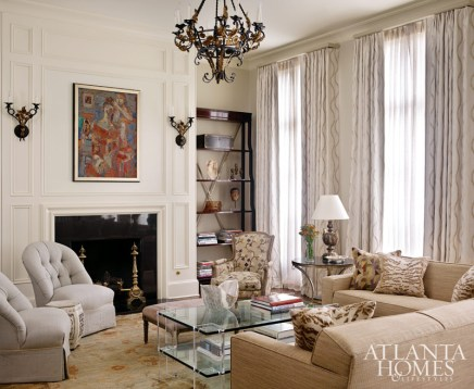 The living room draws interest from layered textures and contrasting elements, such as a Lucite coffee table, gilded-iron lighting, and mismatched throw pillows from Cowtan & Tout and Glant.