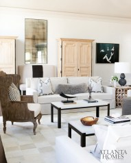 """Shawn Broaddus brought the family room down to size with a pair of oversized cabinets and custom Belgian linen-covered sofas by Bjork Studio. The wooden wingback chairs by Mr. Brown are a youthful take on a traditional design. """"I wanted the couple to feel like the house fit their personalities,"""" she says."""