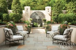 Beyond a set of rich mahogany Palladian doors on the ground-floor level of this four-story townhouse is a private, English-inspired courtyard, secluded in feel thanks to the sound of a fountain, identical seating areas and just the right amount of landscaping by Edwin Rabine.