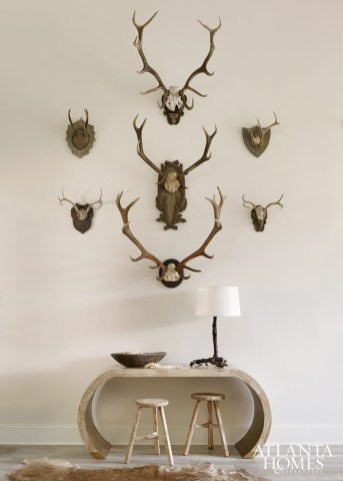 Small and large wall-mounted horns mingle to create one cohesive statement in the foyer. Console, Mrs. Howard. Stools, South of Market. Root lamp, mounted horns and beads, A. Tyner Antiques. Hide rug, Bungalow Classic.