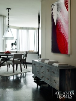 A contemporary painting by Sharon Weiner presides over a midcentury modern console; the arrangement eases the transition from hallway to dining room.