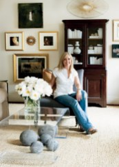 """Designer Courtney Giles perches in her living room, which houses the majority of her art collection. Gold sunburst, Belvedere, (404) 352-1942. Art, JF Baldwin and Jean-Pierre Bourquin, Galerie Timothy Tew, (404) 869-0511. Armless chair, O""""Henry House, Travis & Company, ADAC, (404) 237-5079. Rug, Designer Carpets, ADAC, (404) 262-1720. Lucite coffee table, Travis and Co."""