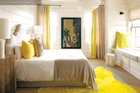 """With pops of sunshine yellow and views of the lake, this bedroom""""s cheery disposition makes it a favorite of overnight guests. Painting by Cynthia Packard."""