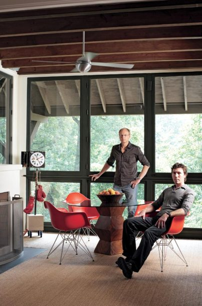 """At first, we were going to leave this as a screen porch,"""" says Todd Pritchett (standing). """"Then we decided to make it more convertible; the screens pop in so you can make it into a screen porch. And with the wide overhangs, even in a storm you can leave the windows open."""" Partner Craig Dixon, also of Todd Pritchett Design Studio, is sitting. Eames Eiffel Armchairs by Herman Miller, CWC, (770) 493-8200. Sculpture by Jeff Jones, Jeff Jones Design Inc., (404) 731-8068."""