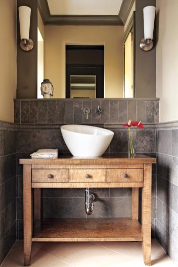 The powder room features wainscoting made of Portuguese limestone, a handsome backdrop for the custom bird's-eye maple cabinet. Cabinetry, stained bird's-eye maple, by Phil Plunket Custom Cabinetry. Wall faucet, Falling Water by Kohler. Sink, Crucible by Kohler. Lights, Marina from DWR. Wainscoting and floor, Walker Zanger.