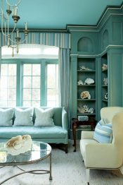 One of the more formal rooms in the house is the study. Sliding doors, a hidden TV and a fireplace make the room a personal sanctuary. Roberts painted the ceiling Tiffany blue, and finished the walls with delicate layers of aquamarine-blue, for a serene depth.