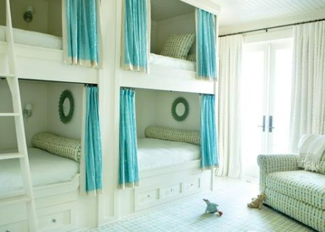 """""""Beach houses are all about having fun,"""" says Kay. Double bunk beds in the girls"""" room provide more than mere sleeping spots; the curtained bunks each have reading lamps and mirrors for primping."""