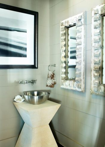 In lieu of a more traditional pedestal sink, Kay fashioned one from an angular table and a simple stainless-steel bowl. And, in another twist of convention, she hung a water-themed photograph over the washstand; mirrors are a mere quarter-turn to the right. Framed photograph, Ashley Waldron Hope, Davis Waldron.