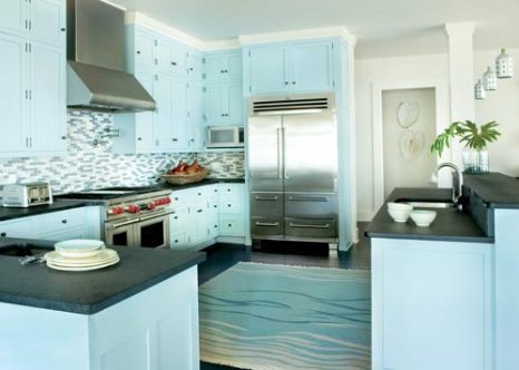 Flamed black granite countertops provide hard-working, easy-care surfaces in the kitchen. Their dark hue anchors the pale blue color of the cabinetry.