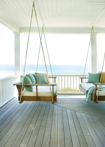 """A set of French doors in the master leads to a wraparound porch, where extra-long twin mattresses cushion a pair of swings""""perfect for curling up with a book or catching a nap."""