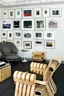 The family room is a study in modern classics, including the Saarinen Womb Chair and Ottoman, Frank Gehry's Power Play chair and ottoman, and a Saarinen Side Table. The wall is a collage of personal photographs.