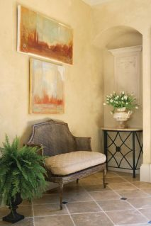 An antique cane settee in the foyer is set off by two fresco-style paintings from Jeff Littrell Ltd.