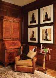 """""""In the library, an antique leather chair pairs well with a grouping of figurative paintings, while the dark stained walls complement the lighter burled finish of the secretary,"""" says the designer. """"The muted Oushak rug warms the room and helps to create a comfortable nook for reading or playing chess."""""""