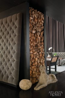 Forming a boundary between the living and dining areas, a tower of stacked firewood takes on the appearance of an art installation.