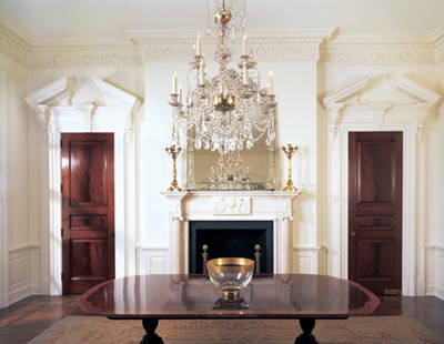 The focal point of this Harrison-designed dining room is a hand-carved marble mantle with fluted friezes and columns. The cornice contains traditional egg and dart molding combined with fluted friezes embellished with rosettes.