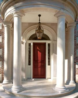 A semicircular porch is detailed entirely with Indiana limestone, including Doric columns that support a curving entablature and fluted Ionic pilasters that frame the mahogany door.