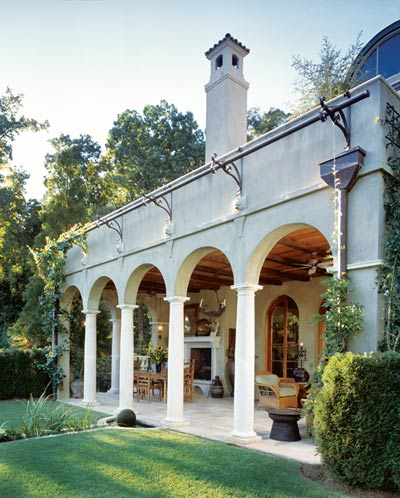 """Harrison""""s personal home in northwest Atlanta features Italian influences, but its design has been adapted to this region""""s climate and geography and its specific site in Fulton County. A decorative trellis running the length of the loggia""""s arched openings supports the growth of muscadine vines and roses, offering lush seasonal color and fragrance."""