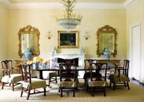 Blue-and-white ceramic urns were used as accents throughout the house, adding an exotic touch to the dining room when combined with the foo dog figurines on the mantel. Slipcovered dining chairs and a broad sisal rug impart a relaxed aura to the otherwise formal space.
