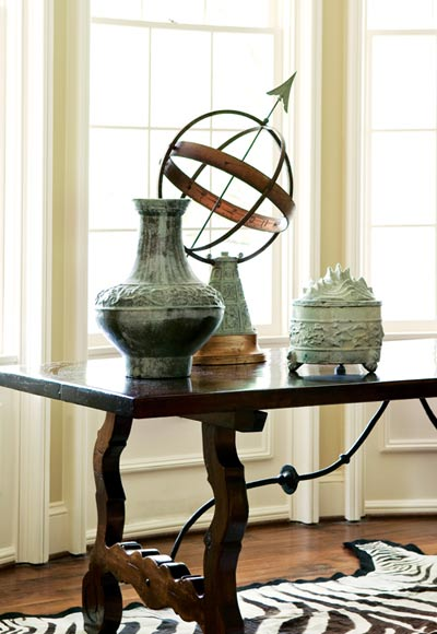 "Set on an intriguing Spanish table, a collection of aged verdigris pieces""including an armillary sphere""serve as playful complements. A zebra skin rug adds the sort of flair and fun that makes the family feel right at home."