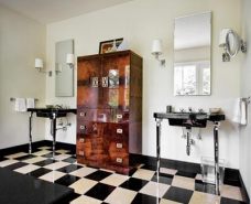 """The master bath features timeless details, including a unique floor pattern inspired by one Holman saw in a David Adler-designed house in Chicago. Holman chose this beautiful root-cut walnut bachelor""""s chest from Belvedere over traditional built-in cabinets for storage. Hinson sconces flank the mirrors and Kohler vanities."""
