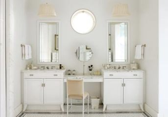 The marble-clad master bathroom features custom cabinetry designed by Katie. She had the nickel hardware cast from the drop of an Art Deco chandelier. The vanity chair is by Warren McArthur, a designer whose work helped define the Art Deco era.