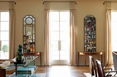 """Mirrors were fashioned out of 19th-century French window frames that Katie found in Charleston. Two vintage Tommi Parzinger lamps from Belvedere sit atop a pair of 19th-century demilunes. The glass console is Italian. There""""s a sense of modernity throughout the house, but its scale and proportion harken to the timeless principles of classic design."""