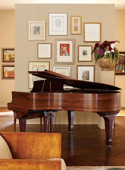 """Near the Steinway piano, some of Katie""""s favorite art is hung salon style. """"My grandmother was a board member of The Metropolitan Museum of Art,"""" says Katie. """"Three of the pieces, including a Renoir and a Picasso, were gifts to her for serving."""" The majority of the other art came from Tew Galleries."""