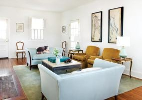 """The living room is spare but verdant, thanks to soothing shades of blue and green. A pair of settees, which once belonged to Elizabeth's grandmother, now finds peaceful repose in aquamarine. The doors on either side of a pair of caramel-colored armchairs were once windows, but the couple had them converted to soften the boundaries between indoors and out. In the spring, it's wonderful to open up the screen doors and let in fresh air,"""" says Andrew. Even closed, a door just feels different from a window. Custom steel table with limestone top."""