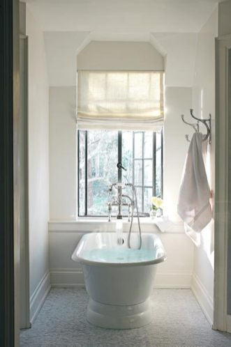 """The master bath, like much of the house, is awash with natural light and timeless appeal. Although some square footage was forfeited to make room for the master closet, there""""s still plenty of space for all the essentials""""and then some. Floor tiles, Waterworks."""