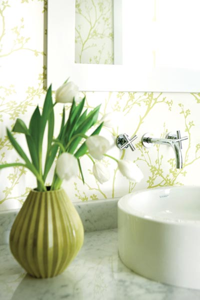 This guest bath was given a vibrant treatment with spring green wallpaper from Schumacher, adding visual interest to the otherwise understated space.