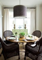 In the dining room, wicker chairs from Mainly Baskets have an open weave that keeps the look light and airy. At the same time, their dark chocolate hue, repeated on the custom drum shade above, lends dramatic impact.