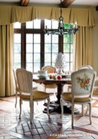Playing off the coffered ceilings found throughout the house, the breakfast room floor features terracotta tiles set within crisscrossing bands of wood, lending a divinely rustic texture.