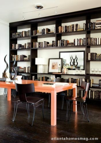 "The dining area doubles as a handsome library, complete with floor-to-ceiling shelves that serve up space for a bar or buffet. But the ""pieces de resistance"" is a custom Parsons table with an orange lacquer finish."