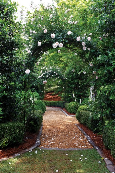 This view through the parterre garden leads through arches covered with New Dawn climbing roses mixed with Will Goodwin clematis. Korean boxwoods, granite cobblestones and American boxwoods line the pea gravel path. opposite New Dawn roses embody the sense of serenity found in this garden.