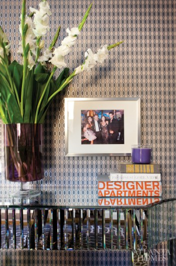 """At the entry of the assistant""""s office is a mirrored console from hayneedle.com, accessorized with a framed photograph of Jenner Communications employees enjoying a night out on the town."""