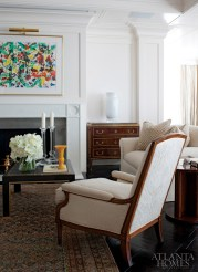 In the living room, a painting by Sam Francis hangs above a marble-and-stainless steel fireplace designed by Stan Topol & Associates and fabricated by Francois & Co. The 19th-century Russian chest, from Karl Kemp & Associates in New York, is part of a pair. The 1930s bergere, by Jansen, is from Dragonette in Los Angeles and upholstered in a Christopher Hyland fabric. An antique Khotan rug from Moattar, Ltd. anchors the space. The round Art Deco table is from Karl Kemp & Associates. Floral design by Michal Evans.