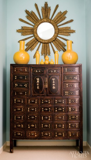 "Huff notes that ""brown woods have so much life"" when placed against the hallway""s light aqua walls, while Dewberry appreciates the hue""s ability to bring colorful accents like their collection of yellow porcelain into sharp focus. A Chinoiserie cabinet, purchased from a local antiques store, houses trim samples."