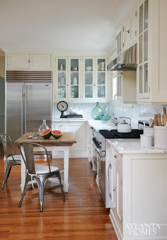 The Barfields' eat-in kitchen features statuary marble countertops from Bottega Stone, a porcelain farmhouse sink and simple Roman shades that filter in soft light. Glass-front cabinets provide a glimpse of her favorite china and creamware.