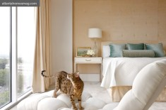 A gold velvet-upholstered wall adds warmth and sophistication to the master bedroom, a favorite perching spot for Alley the cat. Bates and Corkern designed the bedside table; Michael Morrow fabricated it for the space.