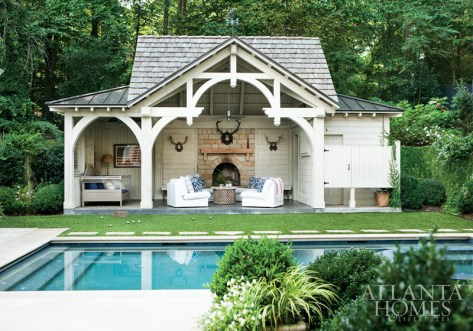 A fireplace surrounded by a stone hearth is the focal point of the family's favorite hangout spot, the pool pavilion. Upholstered seating, which Pearce found at Ikea, is clustered around a West Elm coffee table.