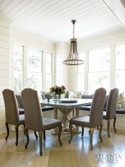 A corner banquette, armless chairs and a zinc-topped table by Kevin Stanton create a cozy nook off the updated kitchen. The chandelier is from Boxwoods.
