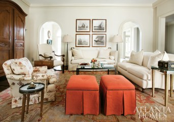 An antique Oushak inherited from Tom Pearce's parents influenced the room's palette of faded neutrals and pops of persimmon. A quartet of antique ship etchings hangs above the loveseat.