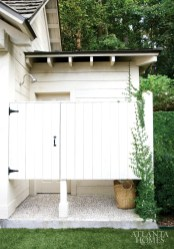 Evoking a New England summer cottage, the outdoor shower features exposed rafter tails and shiplap paneling.
