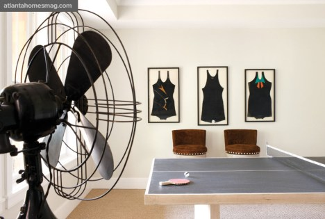 Framed vintage swimsuits from A. Tyner Antiques overlook the custom ping-pong table. Onlookers can watch a game while seated on the Verellen barstools. Table and chairs available through Bungalow Classic.
