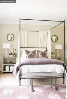 The finishes on the painted bedside tables and rough-hewn bench are in perfect juxtaposition with the more refined textures of the iron bed and crisp linens. Soft, sophisticated color was added to the room by mixing in plush throw pillows, a soft coverlet and a Madeline Weinrib rug. All furnishings, Bungalow Classic. Artwork by Doug Trump, represented by Emily Amy Gallery.