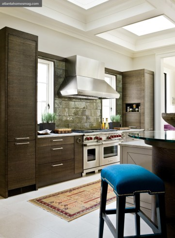 """Form & Function Kitchen, Christy Dillard Savvy concealed storage flanked a Wolf range, the heart of the chef""""s kitchen. Unique stone and wood selections added finesse and �?©lan to the utilitarian space."""