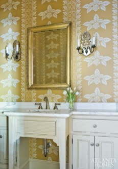 A warm marigold wallcovering graces the powder room, beautifully complemented by bright white marble-topped cabinetry. Shedding light on the space is a pair of antique Venetian sconces from Edgar-Reeves.