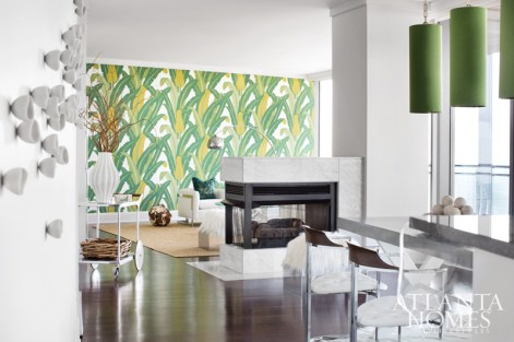Schumacher's Tropical Isle wallcovering makes a dramatic statement in the living room of this Buckhead abode. Lee Kleinhelter balanced its scale with natural elements, such as the pearlized teak ball and a woven area rug.