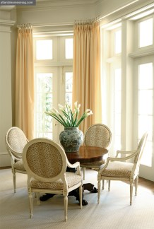 """In quintessential Essary & Murphy style, classic furnishings set against a soothing neutral backdrop are as comfortable as they are comforting. At one end of the living room, a 19th-century pedestal table is surrounded by painted French armchairs, decked out in Cowtan & Tout's """"Ocelot"""" for a modern-day twist. Drapery fabric is by Duralee."""